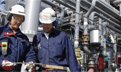 two men in PPE inspecting something with pipelines in the background to represent J&E Hall's oil and gas industry page.