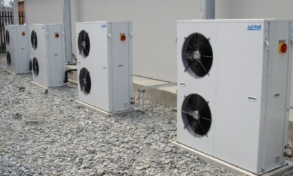 multiple J&E Hall cooler units outside a building that's used on J&E Hall's about us page.
