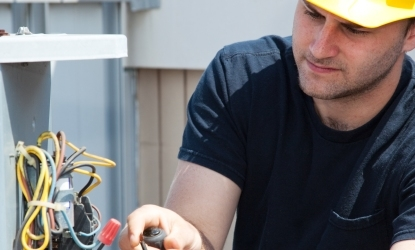 view of a man with a hard hat installing some wires on a air conditioning unit.