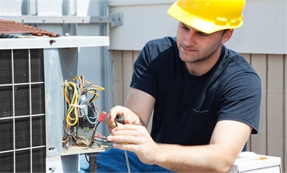 view of a man with a hard hat installing some wires on a piece of equipment.