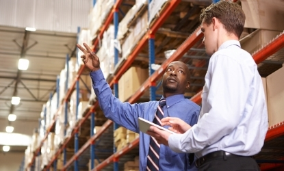 man pointing up to racking in warehouse to another man to represent J&E Hall's range of parts.