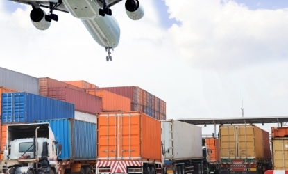 a plane flying over shipping containers and lorries.